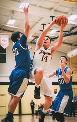 Lansing Christian School Senior Josh Parks fights off two defenders to make a lay up