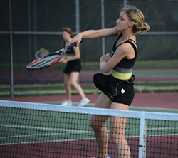 Lansing Christian School tennis player Claire slams a return of a serve
