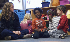 Lansing Christian School Preschool students playing with a high school teacher's aide.