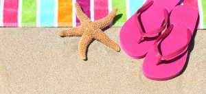Tropical beach vacation holiday and travel concept with a colourful striped beach towel and vibrant pink sandal flip flip thongs on pristine sand with a starfish at an idyllic coastal beach resort.