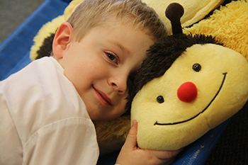 Lansing Christian School Daycare student snuggling with his stuffed toy