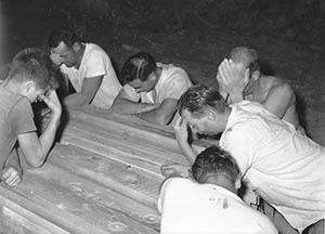 Men praying over wood used to build original school building