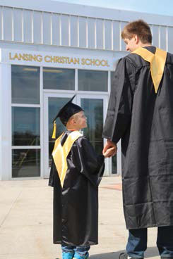 Lansing Christian School Kindergartener with his graduating Senior Buddy