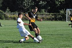 Lansing Christian School soccer player Nick Jamieson beats his opponent to the ball